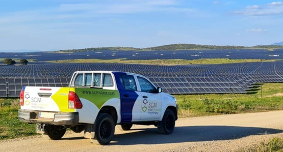 Camioneta de scm delante de un campo de placas solares